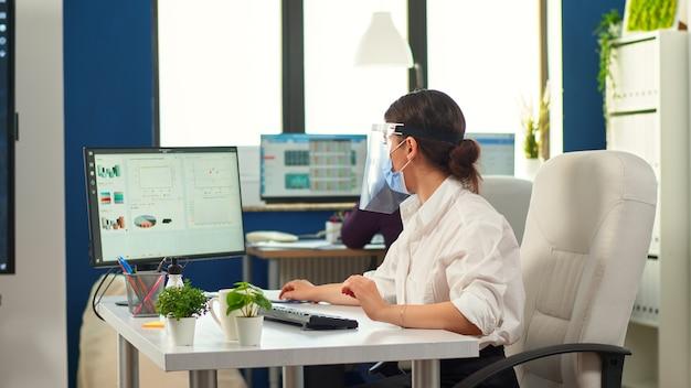 Colleghi con maschere di protezione che lavorano insieme sul posto di lavoro durante la pandemia. squadra nel nuovo normale ufficio finanziario aziendale digitando sul computer, controllando i rapporti, analizzando i dati guardando il desktop