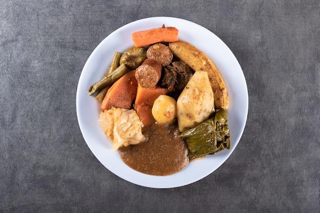 Cozido è un piatto di cibo brasiliano su tavola grigia e vista dall'alto.