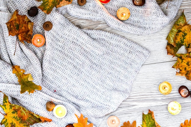 Accogliente sfondo autunnale. maglione bianco con foglie secche e candele. copia spazio. posto per il testo. vista dall'alto
