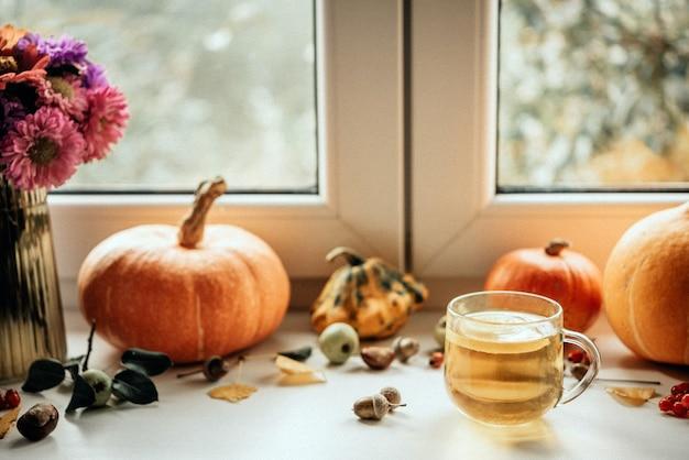 Accogliente composizione autunnale con una tazza di tè al limone zucche e ghiande
