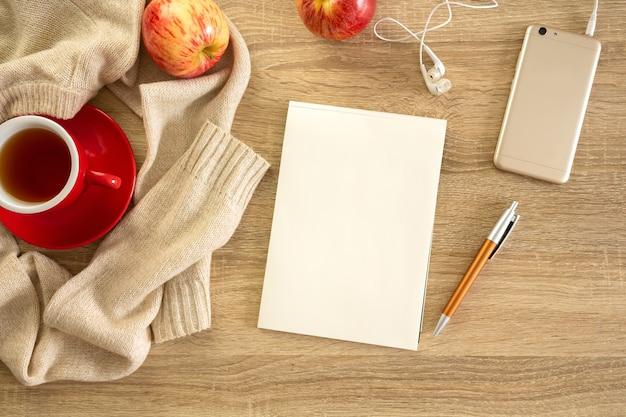 Accogliente composizione autunnale con mockup di notebook, maglione e tazza di tè.