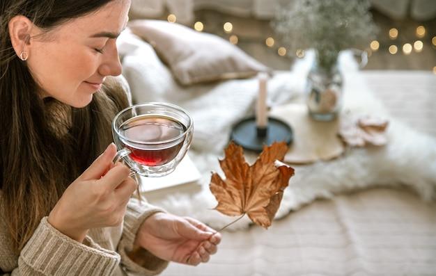 Accogliente atmosfera casalinga autunnale, una donna con una tazza di tè in mano. concetto di riposo e comfort.