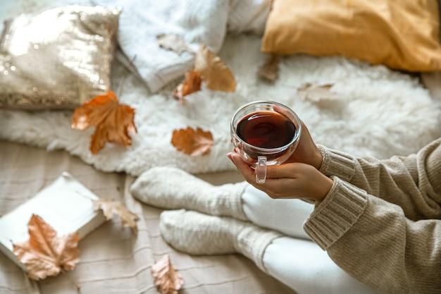 Accogliente autunno a casa, una donna con un libro e un tè a riposo. uno stile di vita accogliente. parti del corpo nella composizione.