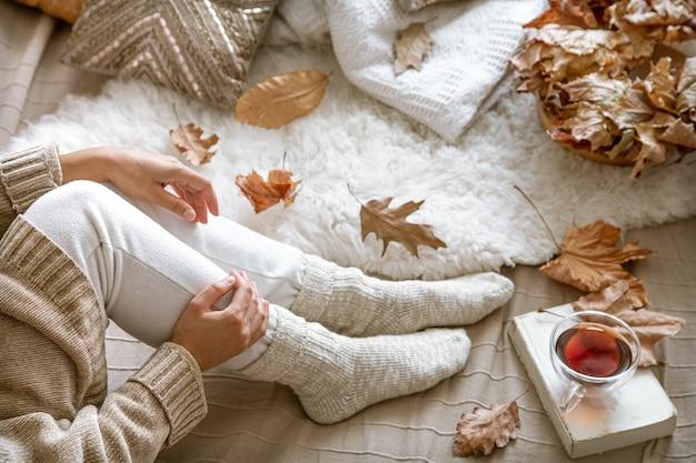 Accogliente autunno a casa, una donna con un libro e un tè a riposo. modo di vivere accogliente.