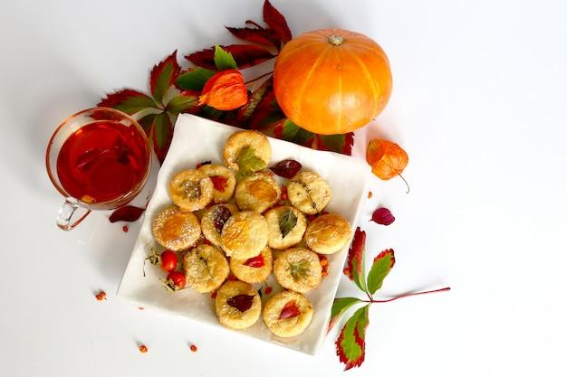 Accogliente scena d'atmosfera autunnale con foglie secche. biscotti fatti in casa con tè, foglie di autunno e zucca
