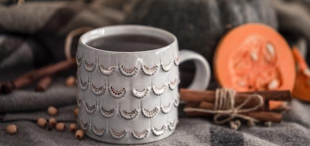 Accogliente autunno ancora in vita con tazza di tè e zucca, con bastoncini di cannella su un caldo plaid, un concetto nella stagione autunnale o invernale