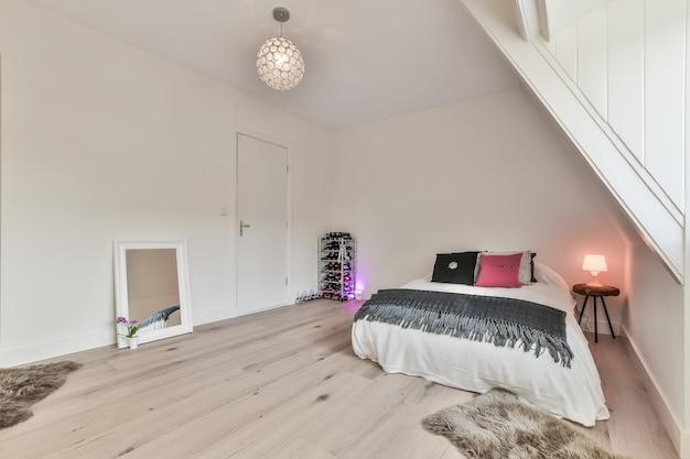 Letto accogliente posizionato in un angolo della camera da letto moderna in stile minimalista con pareti bianche e soffici tappeti su pavimento in legno e con illuminazione colorata