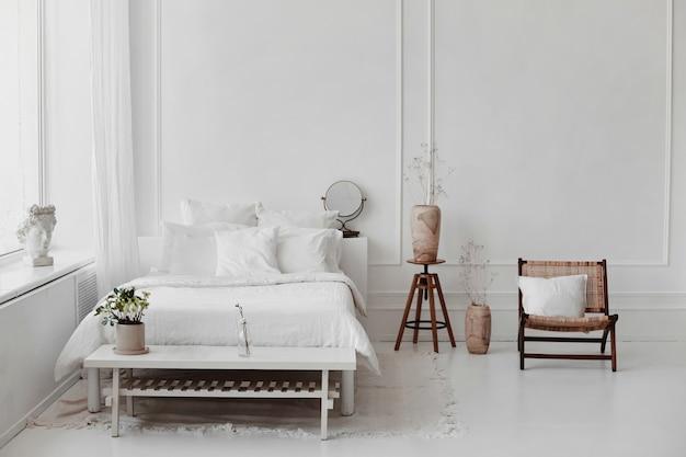 Interno accogliente della camera da letto di un tavolino da caffè in legno con poltrona vintage con fiori in un letto leggero in vaso e altri accessori decorativi