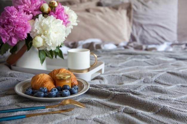 Accogliente colazione a letto, tazza di caffè, mirtilli, marmellata e croissant sul letto grigio. pioni rosa e bianchi nel vaso.