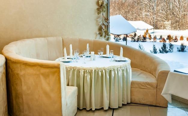 Accogliente divano caffè in piedi intorno a un tavolo apparecchiato per cinque persone si trova contro una grande finestra con un paesaggio positivo sui pendii innevati. concetto di vacanza in un sanatorio
