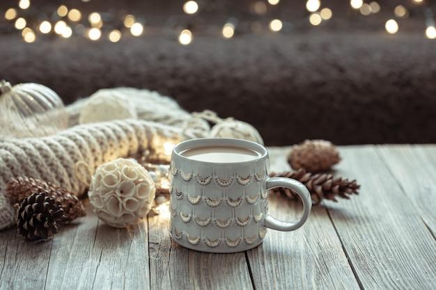 Accogliente sfondo natalizio con una bella tazza e dettagli decorativi su uno sfondo sfocato con bokeh.