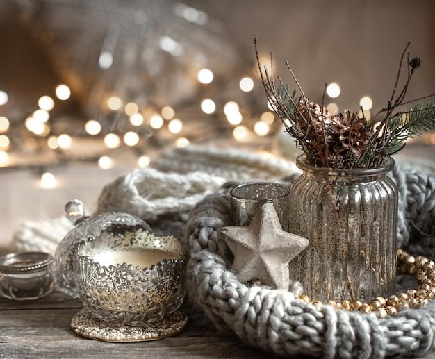 Accogliente composizione natalizia con candele in un candeliere decorativo. il concetto di comfort e calore domestico.