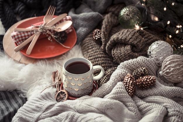 Accogliente mattina di natale con una tazza di tè a letto. scena di natura morta con maglioni. fumante tazza di caffè caldo, tè. concetto di natale.