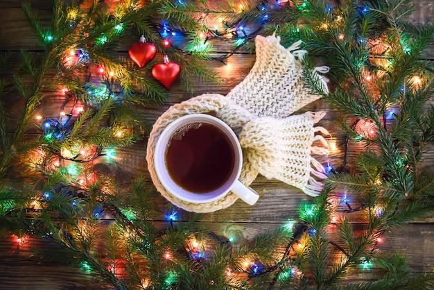 Accogliente foto di natale con una tazza di tè caldo circondata da ghirlande di luci