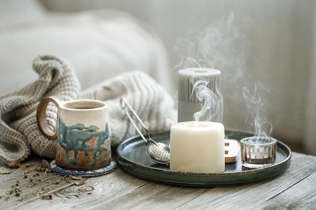 Composizione accogliente con una tazza in ceramica, candele e un elemento a maglia su uno sfondo sfocato.