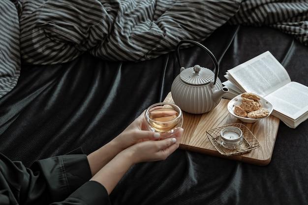 Accogliente composizione con una tazza di tè in mani femminili, biscotti e un libro a letto