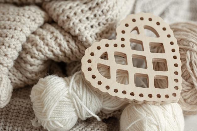 Composizione accogliente con oggetti a maglia e un cuore decorativo in legno da vicino.