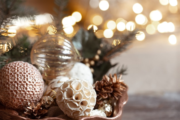 Accogliente composizione con i giocattoli su un albero di natale su uno sfondo sfocato con bokeh. arredamento e concetto di atmosfera natalizia.