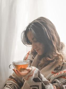 Accogliente tazza di tè la donna nelle mani