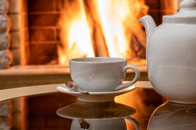Accogliente scena del camino e tazza bianca di tè e teiera su un tavolo, riflesso di un fuoco su un tavolo di vetro.