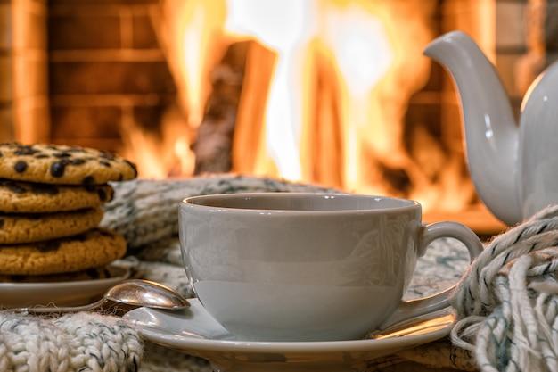 Accogliente scena del camino con una tazza di tè e biscotti su un tavolo, riflesso di un fuoco su un tavolo di vetro.