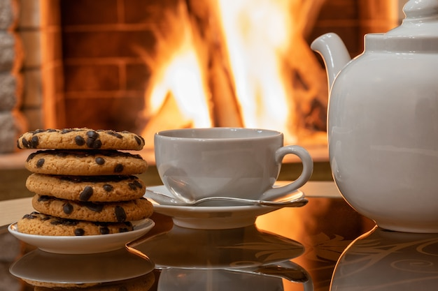 Camino accogliente, teiera e tazza da tè, biscotti su un tavolo, riflesso di un fuoco su un tavolo di vetro.