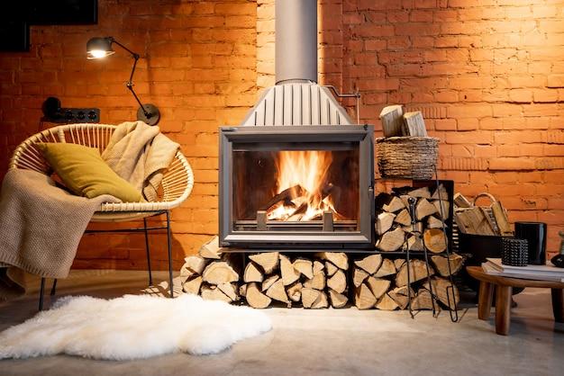 Camino accogliente con legna da ardere nell'interno della casa in stile loft con sfondo di muro di mattoni, fuoco ardente nel camino, intimità della casa in inverno