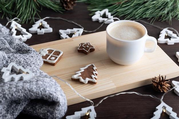 Accogliente tavolo da festa con una tazza di caffè e biscotti di natale. vigilia di capodanno.