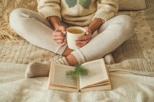 Casa accogliente. la bella donna sta leggendo un libro sul letto. buongiorno con tè e libro. donna abbastanza giovane che si distende. il concetto di lettura
