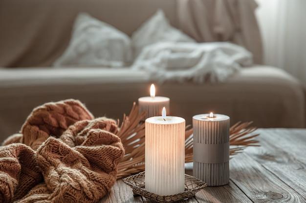 Accogliente composizione domestica con candele accese su un tavolo di legno con un elemento a maglia