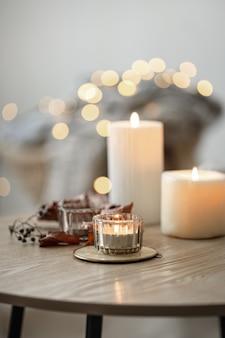 Composizione casa accogliente con candele su sfondo bokeh sfocato.