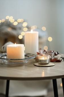 Accogliente composizione domestica con candele su sfondo bokeh sfocato.