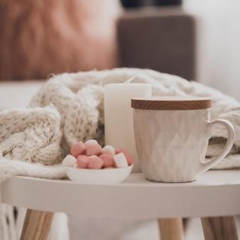 Accoglienti decorazioni domestiche all'interno con maglia e tazza di tè in salotto