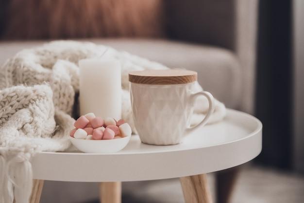 Accoglienti decorazioni per la casa all'interno con lavoro a maglia e tazza di tè nel soggiorno