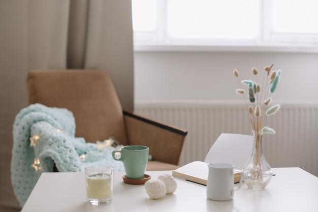 Accogliente interno domestico con una tazza di caffè, un libro e una poltrona