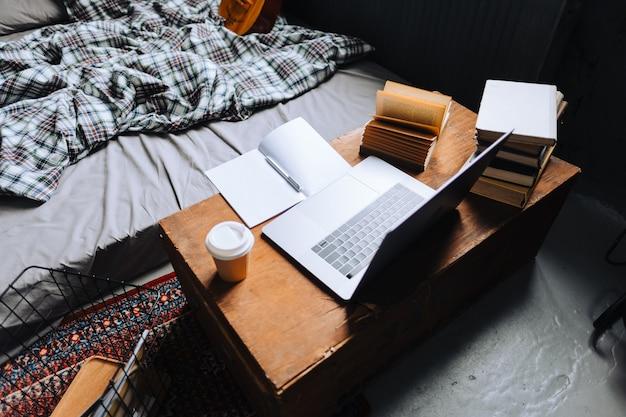Accogliente casa di lavoro con tavolo in legno, laptop e libri vicino al letto.