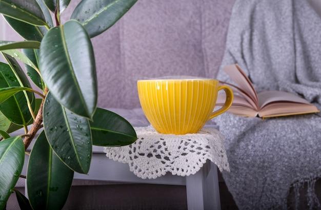Un'atmosfera hygge accogliente e familiare con un divano, uno sgabello, una pianta verde e una tazza.