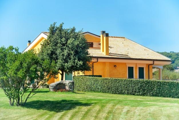 Casa accogliente con giardino, alberi e prato verde
