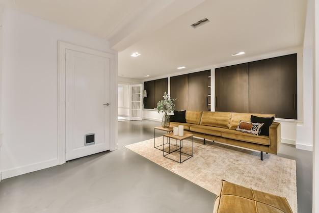 Accogliente design degli interni del soggiorno arredato con comodo divano e tavolo decorato con moquette in un moderno appartamento mansardato con pareti bianche