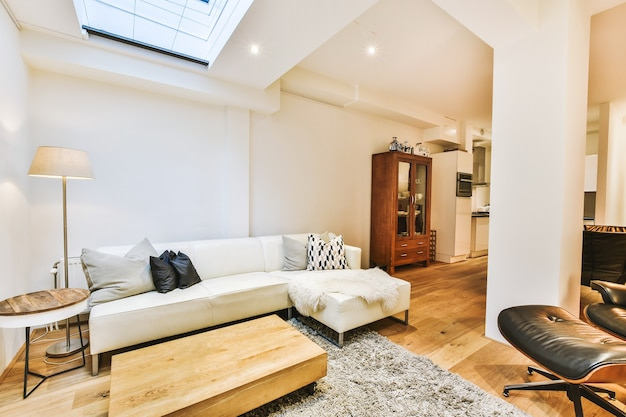 Accogliente design degli interni del soggiorno arredato con comodo divano e tavolo in legno decorato con moquette e lampada in un moderno appartamento mansardato con pareti bianche e colonna