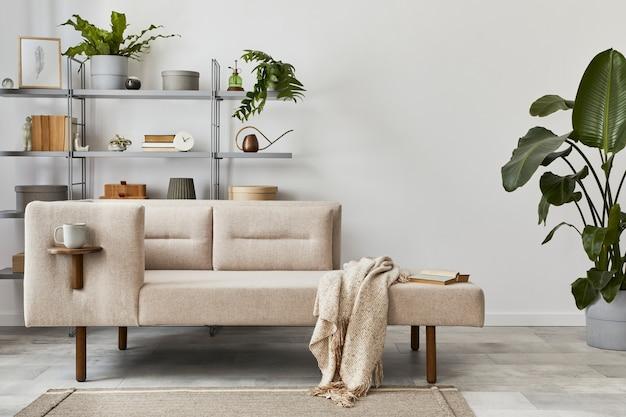 Interni accoglienti con divano elegante, tavolino grigio, libreria, piante, moquette, decorazioni, spazio per copie ed eleganti accessori personali. soggiorno neutro in casa classica. modello.