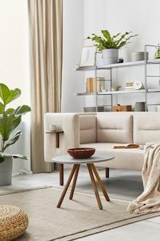 Interni accoglienti con divano elegante, tavolino grigio, libreria, piante, moquette sul pavimento, decorazioni, plaid ed eleganti accessori personali. soggiorno neutro in casa classica. modello.
