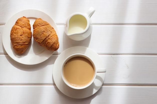Accogliente mattina piatta tazza di caffè con latte e due croissant su un piatto su un tavolo di legno bianco white