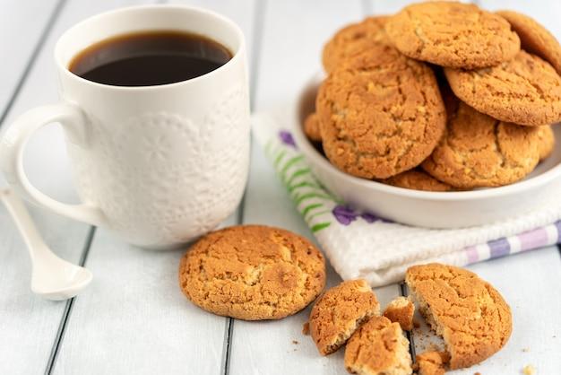 Accogliente natura morta mattutina con caffè nero e una tazza di biscotti di farina d'avena su un tavolo di legno.