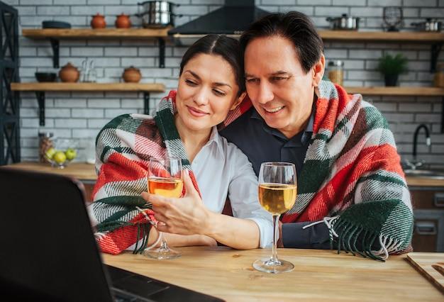 Immagine accogliente delle coppie che si siedono insieme al tavolo in cucina. guardano il laptop e sorridono. le loro spalle coperte di coperta. i bicchieri di vino stanno alla tavola.