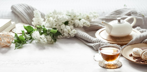 Accogliente composizione primaverile con una tazza di tè, una teiera, amaretti francesi, colore lilla su un tavolo sfocato chiaro.