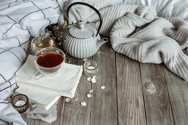 Accogliente natura morta primaverile con candele, tè, bollitore su una superficie di legno in uno spazio di copia in stile rustico.
