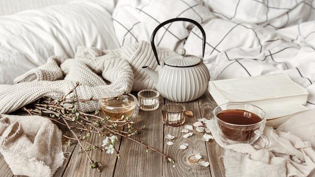 Accogliente natura morta primaverile con candele, tè, bollitore su una superficie di legno in stile rustico.