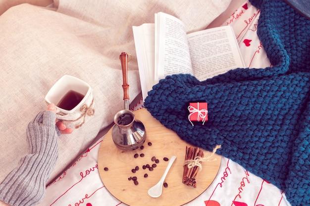 Accogliente natura morta della colazione a letto per il giorno di san valentino. caffè con piccolo regalo e plaid con libro su uno sfondo in periodo di isolamento