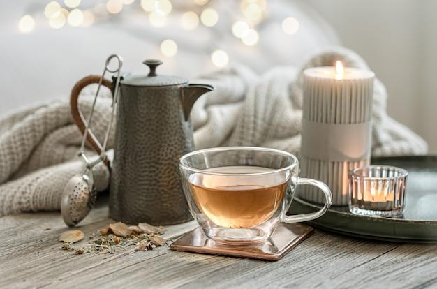 Accogliente natura morta con una tazza di tè in vetro, una teiera e candele su uno sfondo sfocato con bokeh.